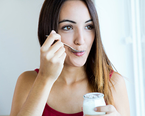 Woman eating yogurt with braces from her Winnipeg orthodontist at Dr. Tim Dumore & Team.